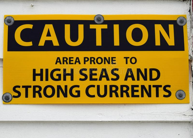 High Seas and strong currents caution sign. Yellow and black warning caution sign, warning of High Seas and strong currents stock images