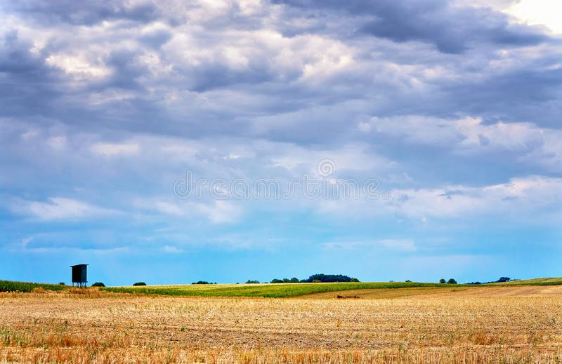 High seat of the hunter on a harvested field in autumn. Clouds over the field stock photography
