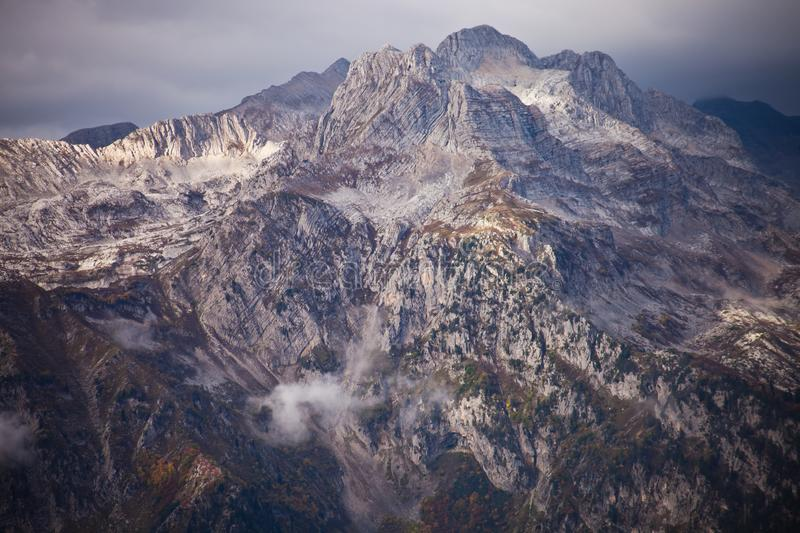High severe stone mountain rocky mountain towers in pieces of. Clouds, harsh beauty stock photo
