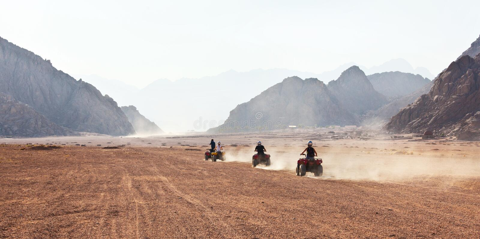 High speed race of several people riding quad bikes in desert royalty free stock image