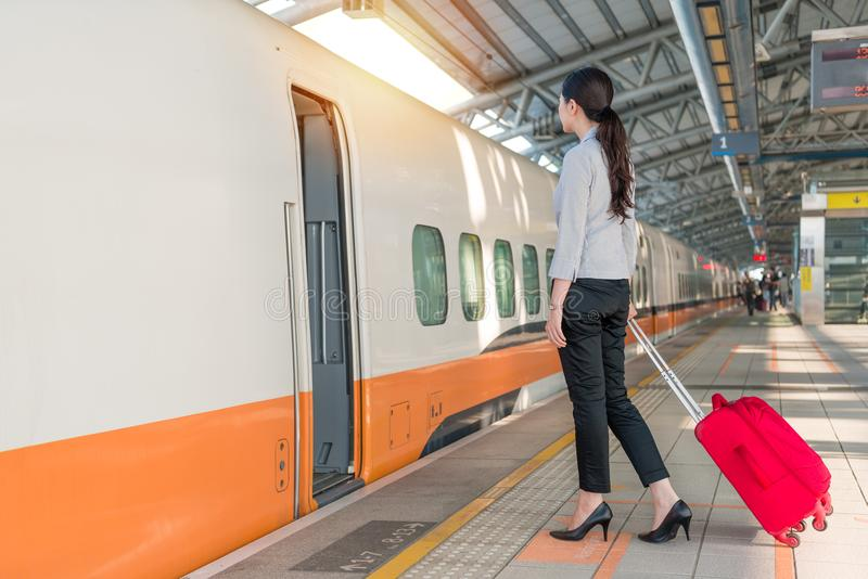 High speed rail train is arriving on station platform. High speed rail train is arriving on the station platform and business office lady ready to get in to royalty free stock photo
