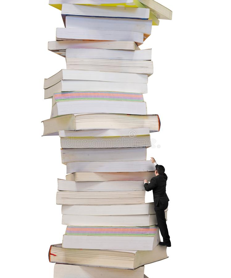 High stack of books with businessman climbing it stock photo