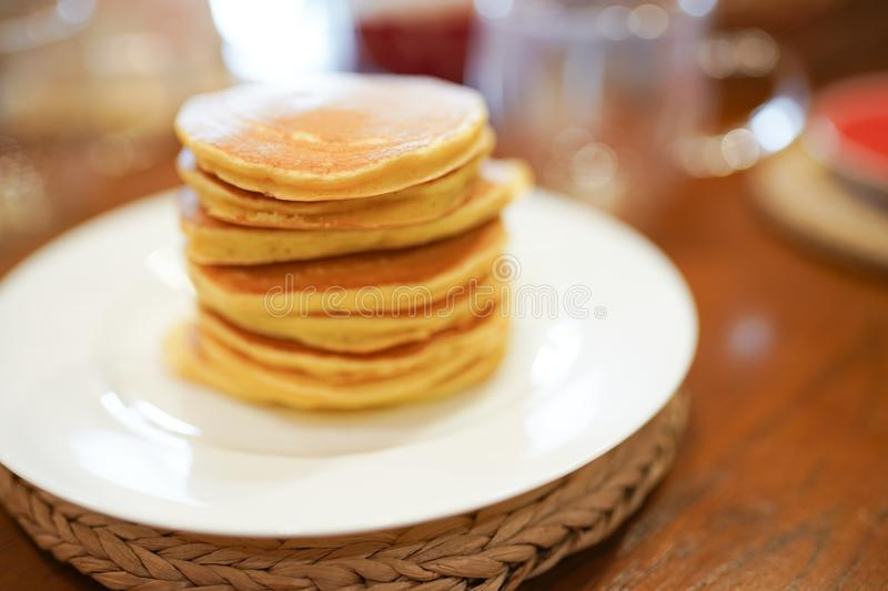 Stack of pancakes on white plate on wooden table in the kitchen . Breakfast or dinner for the whole family. High stack of pancakes on white plate on wooden table stock photo