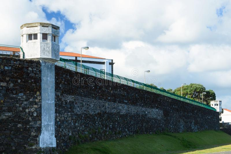 The high stone walls of the prison and the fence in Ponta Delgada, island of San Miguel, Azores. royalty free stock images