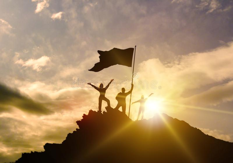 High success, family three silhouette, father of mother and child holding flag of victory on top of mountain, hands up. stock image