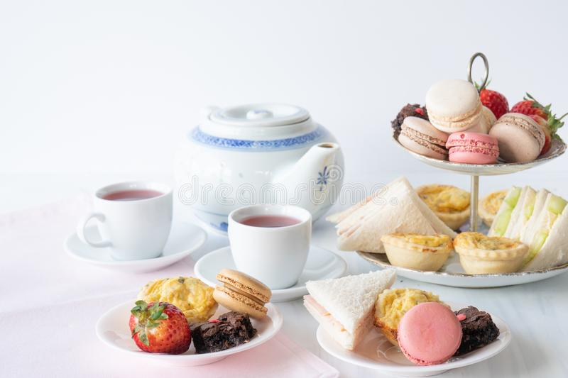 High Tea Horizontal. High Tea with Macaroons, Sandwiches, Quiche, Brownies and Strawberries with Tea Horizontal stock image