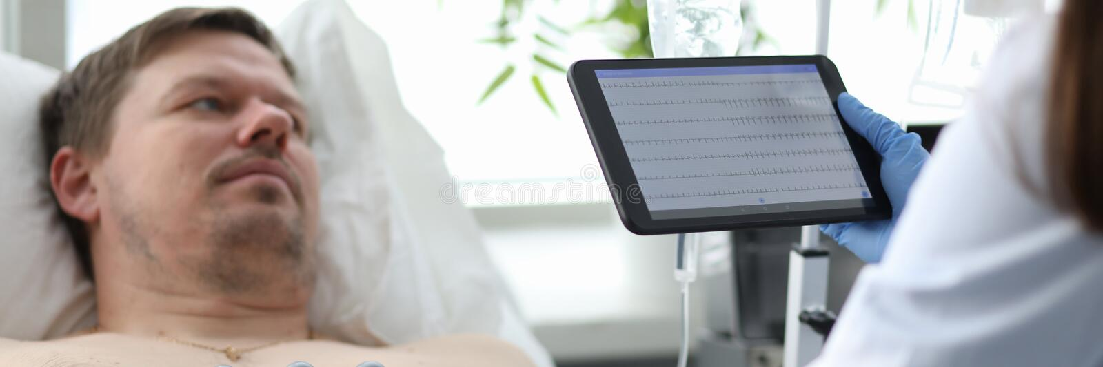 High-tech medical treatment in clinic. Focus on smart woman practitioner looking at newest tablet with medical heart diagram of ill patient and standing in stock image