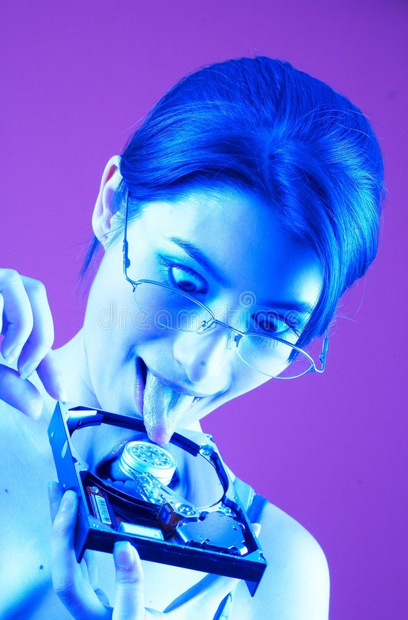 High Tech Taste. Portrait of woman with an HDD with her tongue touching it. Crazy expression. Blue tinted. Isolated on purple background royalty free stock photo