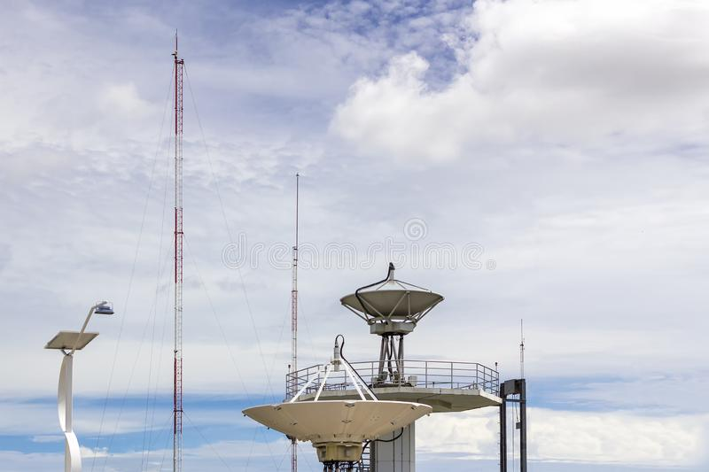 High technology satellite dish station and radio antenna pole on cloudy sky day royalty free stock photography