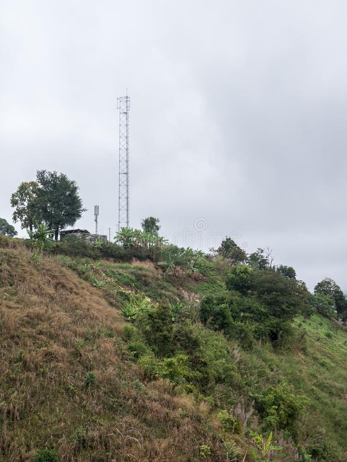 High telecommunication tower on the high mountain. For connection the mobile signal in the local area in the northern of Thailand stock image