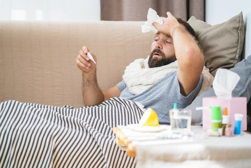 High temperature concept. Man feels badly ill. How to bring fever down. Cold symptoms and causes. Sick man with flu. Man hold thermometer. Measure temperature stock images