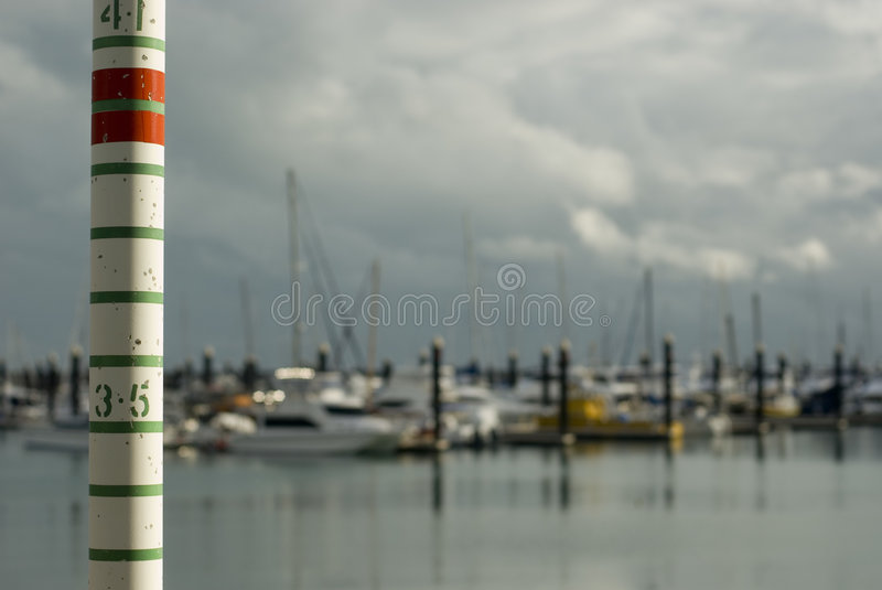 High Tide. Yachts sheltering in a marina with storm clouds. Concept of a'storm surge' rising tide royalty free stock images