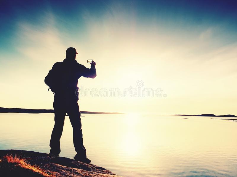High tourist taking selfie on mobile phone against scenic view of sea against evening sky. Sun mirror. In smooth water level. Silent sea bay royalty free stock image