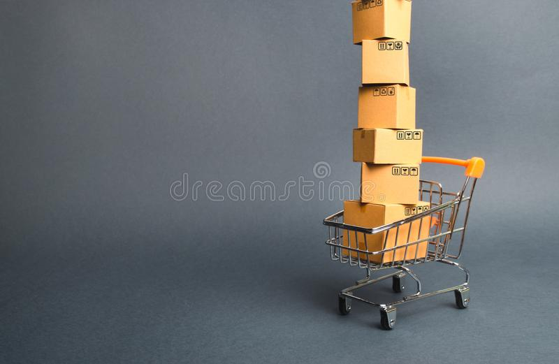 High tower of cardboard boxes on a supermarket trolley. concept of shopping in online store. E-commerce, sales and sale of goods. Through online trading royalty free stock photography