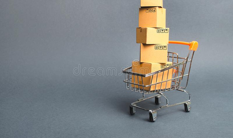 High tower of cardboard boxes on a supermarket trolley. concept of shopping in store. E-commerce, sales and sale of goods through royalty free stock images