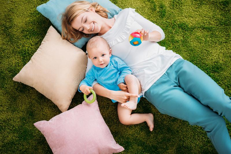 High view of happy mother and child. Lying on green carpet with pillows at home stock photography
