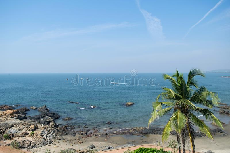 High view landscape with blue sky, sea, green palms at goa beach, coast line background and aircraft trail royalty free stock photos