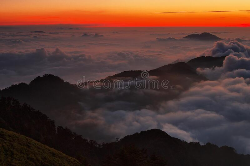 High View Photography of Mountain Ranges Surrounded With Clouds at Golden Hour royalty free stock photo