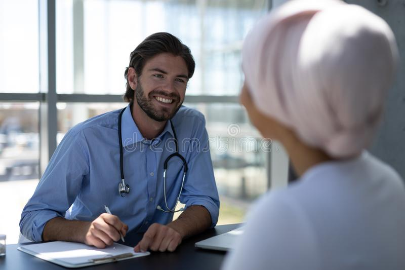 Disabled mixed-race woman and Caucasian male doctor interacting with each other stock photos