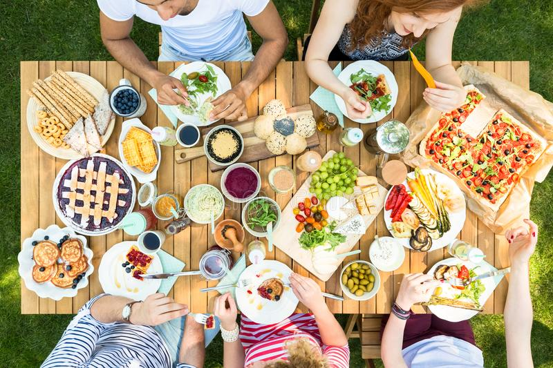 High view of a table with Italian food, eaten by young group of stock image