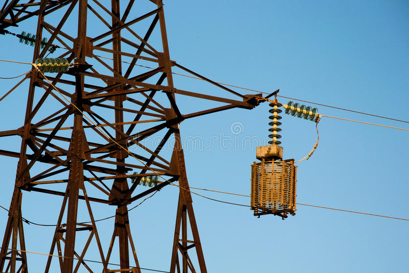 High-voltage column. High-voltage pole against the blue sky. Electrical industry royalty free stock images