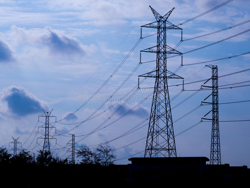 High voltage electric pole isolated in blue sky background stock photos