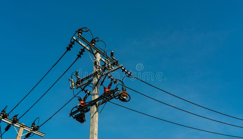 High voltage electric pole and transmission lines with clear blue sky. Electricity pylons. Power and energy engineering system. stock photo