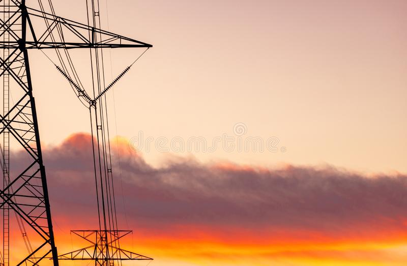 High voltage electric pole and transmission lines. Electricity pylons at sunset with orange sky. Power and energy. Energy. Conservation. High voltage grid tower royalty free stock images