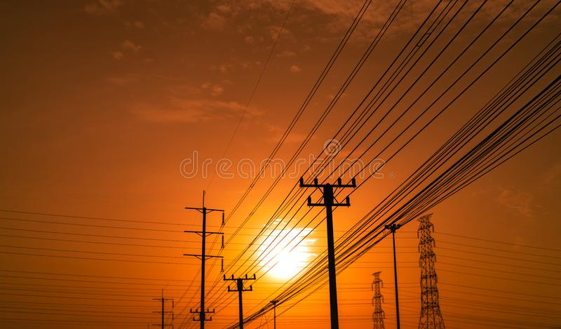 High voltage electric pole and transmission lines at sunset time with orange and red sky and clouds. Architecture. Silhouette royalty free stock photos