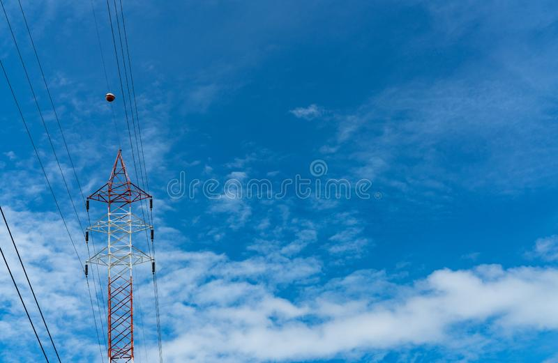 High voltage electric tower and transmission lines. Electricity pylon with blue sky and white clouds. Power and energy royalty free stock photos