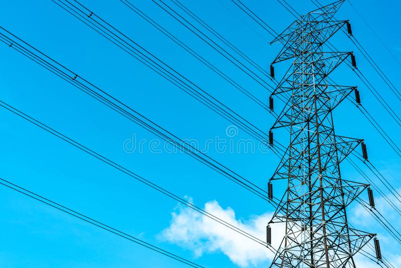High voltage electric tower and transmission lines. Electricity pylons with blue sky and white clouds. Power and energy royalty free stock image