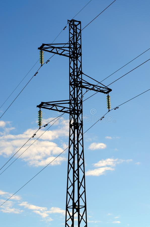 High voltage electric transmission tower against a blue sky stock photography