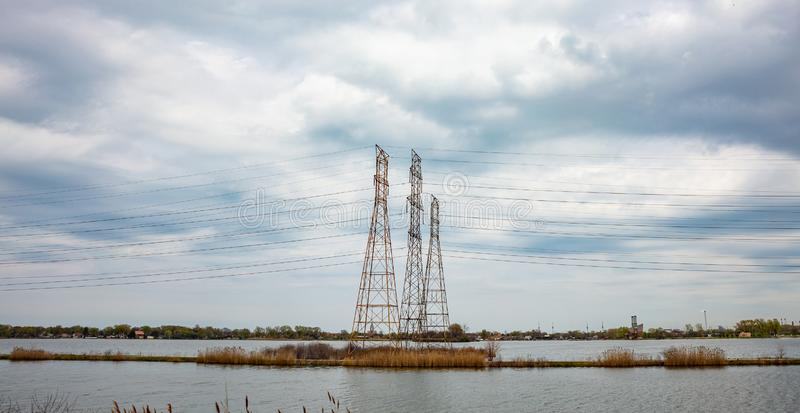High voltage electric transmission towers in a lake, cludy sky royalty free stock image