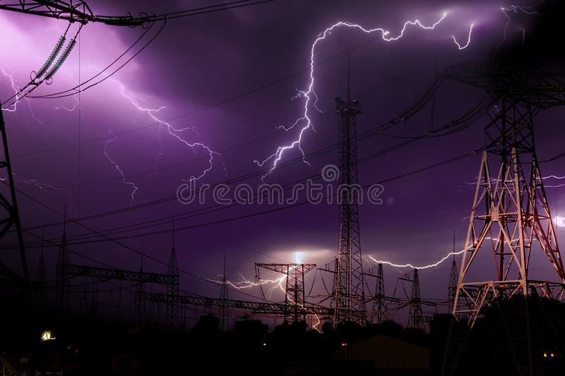 High voltage electrical substation illuminated by lightning flashes during an impending storm at night. High voltage electrical substation illuminated by stock image