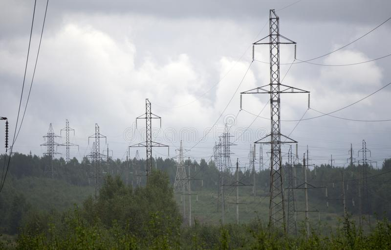 High voltage electrical transmission towers electricity pylons and power lines on green field.  stock image