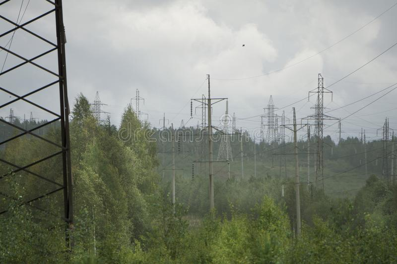 High voltage electrical transmission towers electricity pylons and power lines on green field.  stock photo