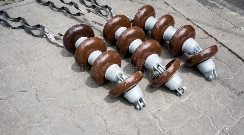 High voltage electricity cable connected with brown ceramic insulators. On cement floor royalty free stock image