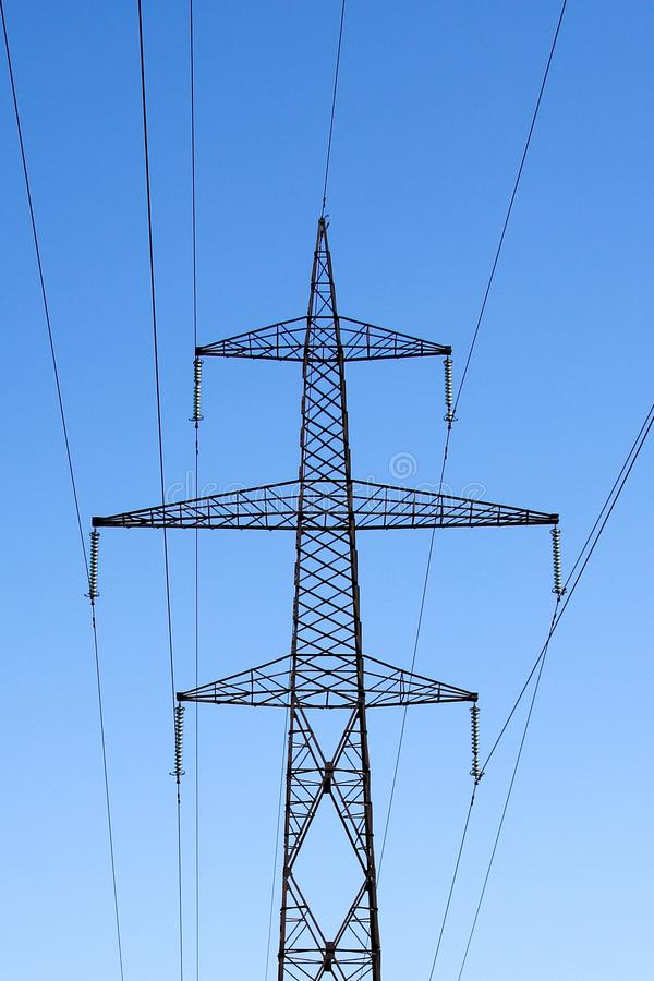 High voltage electricity pole against blue sky. A very tall high voltage electricity line sustained by a big metal pole with lots of wires attached stock image