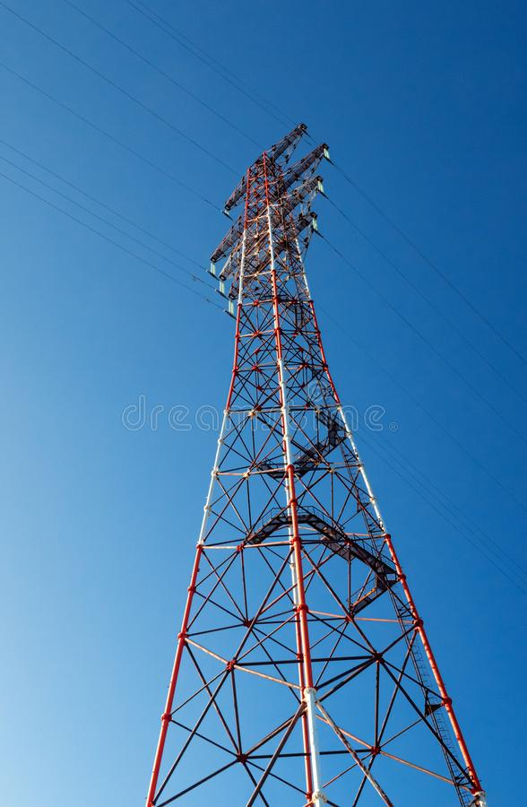 A high-voltage electricity pylon against blue sky at sunny day. High-voltage power transmission tower. Power engineering royalty free stock images