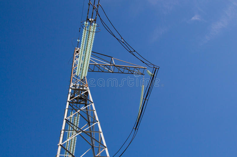 High-voltage insulator of electricity transmission line. Against clear blue sky stock photography