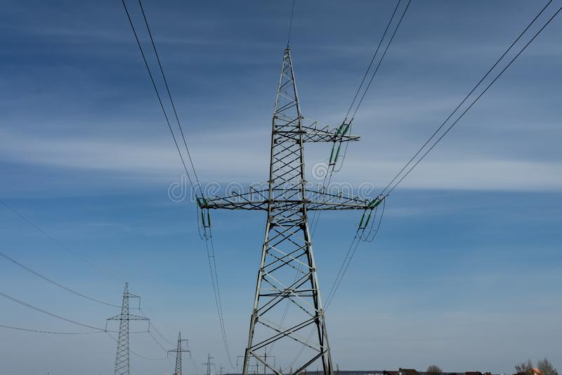 High voltage lines and power pylons on a sunny day with cirrus clouds in the blue sky royalty free stock photography
