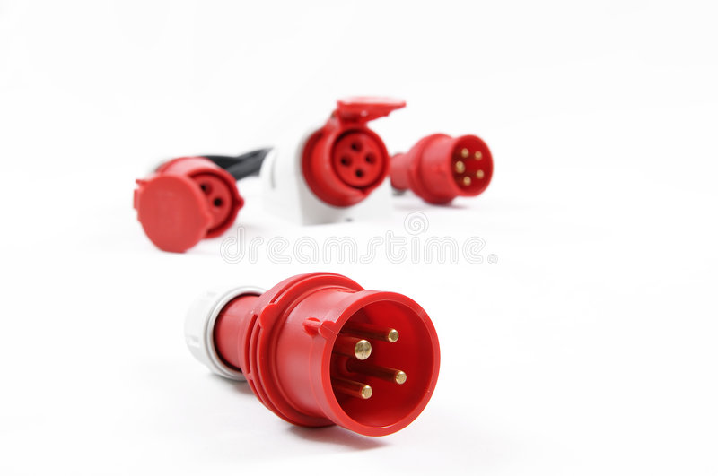 High voltage plug. Closeup of red high voltage plug isolated on a white background. Blurred plug and sockets in the background royalty free stock photos