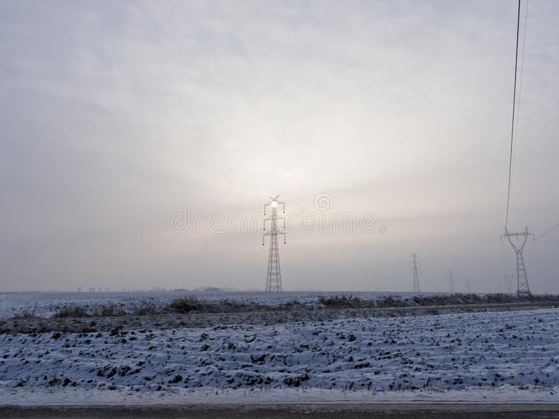 High voltage pole illuminated by a sun hidden in the mist. The December sun has difficulties to break through the clouds stock photography