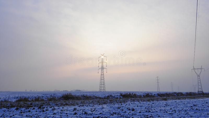 High voltage pole illuminated by a sun hidden in the mist. The December sun has difficulties to break through the clouds stock image