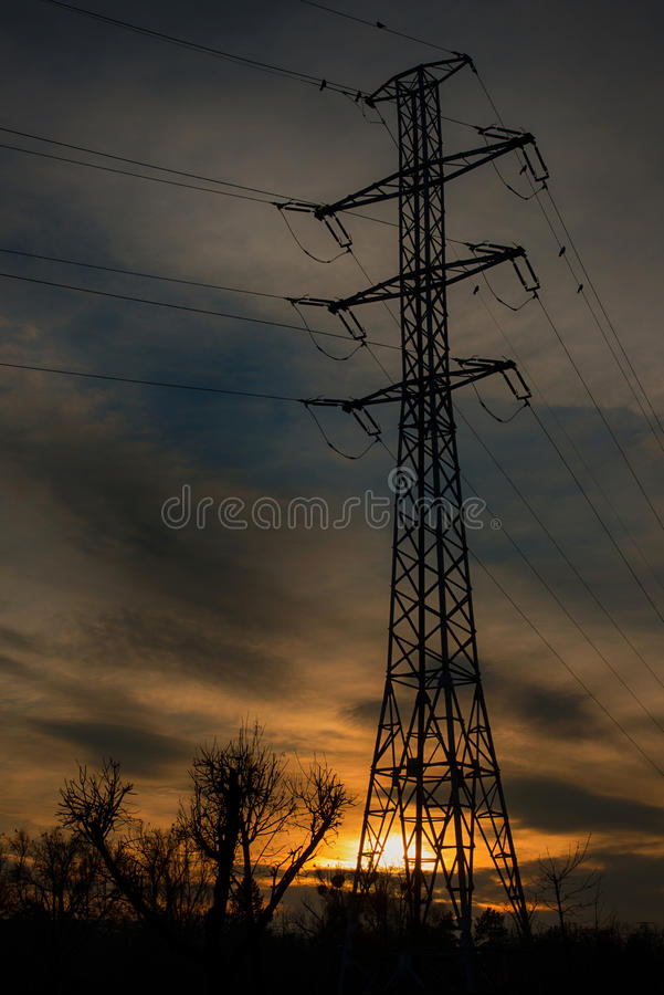 High voltage pole in sunset stock images