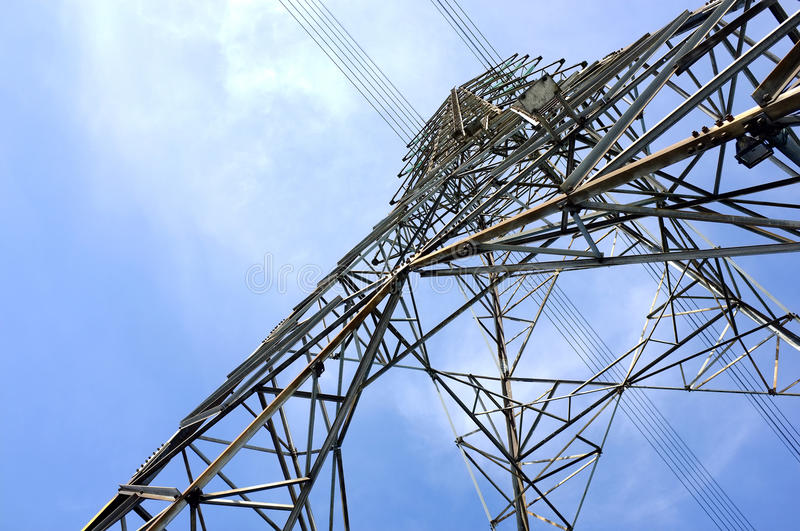 steel frame of high voltage tower with electricity transmission power lines and blue sky royalty free stock photography