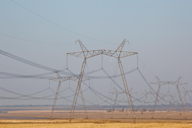 High voltage poles in a row, with a large number of wires are in the desert.  stock image