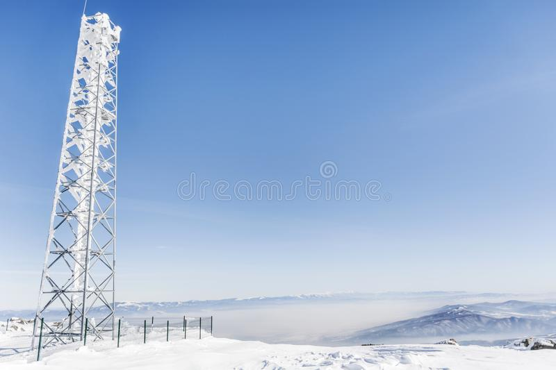 Frozen Power Pole in a Winter Mountain. High voltage post or High voltage tower in a winter snowy mountain stock photo