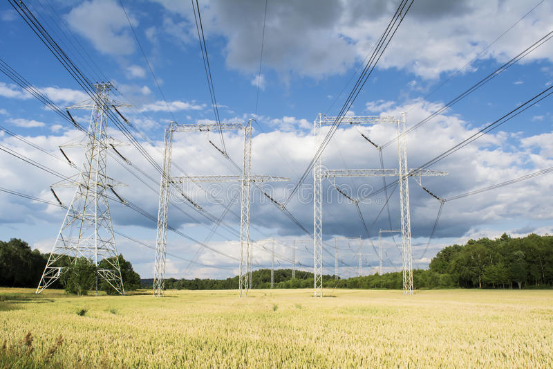High voltage power line in cornfield. High voltage power line from a nuclear power plant standing in cornfield. Modern technology meets traditional farming stock photo