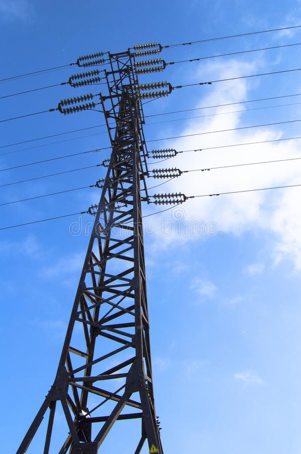 High-voltage power line 110 kV, metal support, wires, insulators, against the blue sky, vertical shot.  stock photo